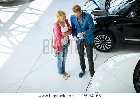 Dealer speaking with a  female client in a dealership
