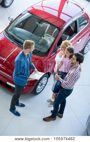 family with car dealer in car dealership saloon