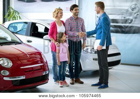 Happy  family buy  new car, car dealer handshaking with daddy congratulated the family on a new car