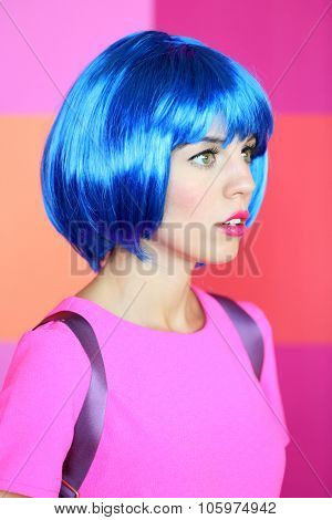 Young woman in dress posing like doll on bright wall background