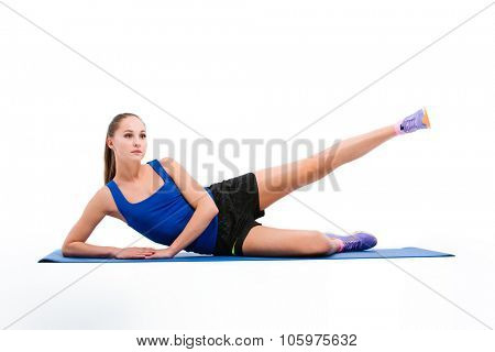 Young beautiful sportswoman in navy top and black shorts doing exercises for legs
