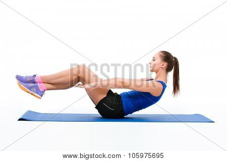 Young beautiful sportswoman in navy top and black shorts doing exercises