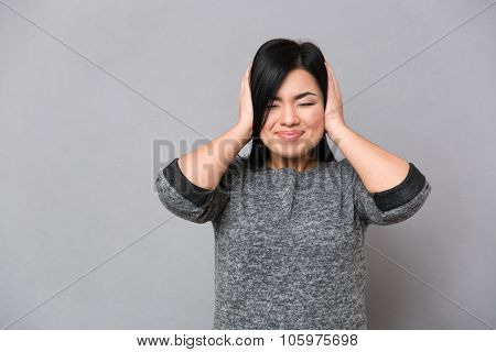 Portrait of a japanese woman covering her ears over gray background