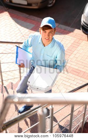 Pizza delivery boy holding boxes with pizza, outdoors