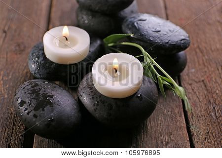 Alight candles on pebbles on wooden background, close up