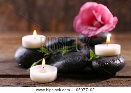 Alight candles, pebbles and fresh aroma flower composition on wooden background