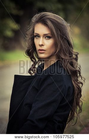 portrait of beautiful long hair young woman  in coat , outdoor in park