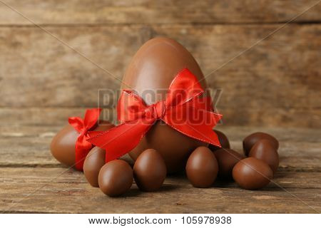 One big and small chocolate Easter eggs on wooden background