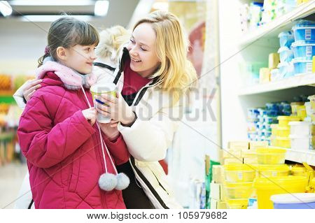 Shopping. woman and girl choosing dairy products in shop supermarket