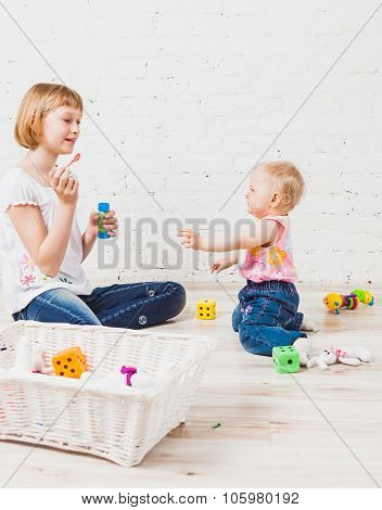 Two siblings playing with bubbles