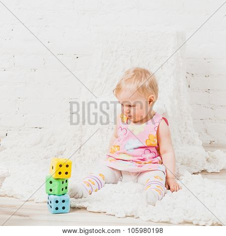 Little baby looking at cubes with dots