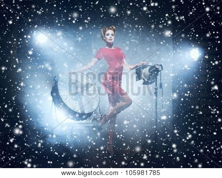 Young and gorgeous actress in fashion dress over glamour background with snowflakes (studio backstage).