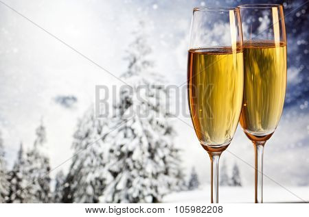 Two champagne glasses and snowy fir trees in the background