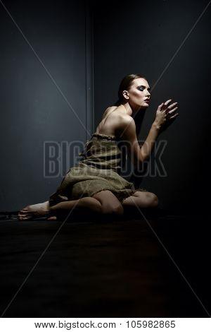 Beautiful skinny model in rags posing as prisoner