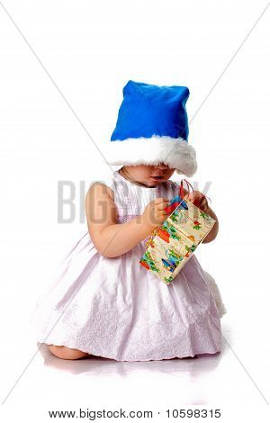 Beautiful Baby In Santa's Hat With A Present