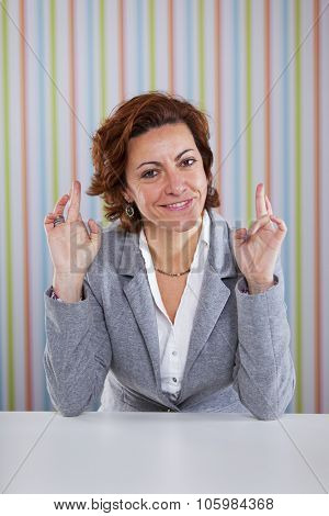 Businesswoman crossing fingers with both hands