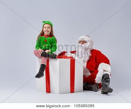 Jolly elf and Santa Claus play together.
