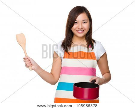 Housewife use of the saucepan and wooden ladle