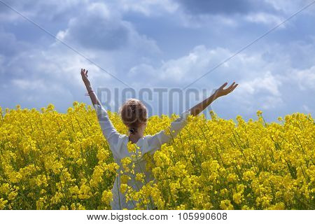 Young Woman Having Fun At Canola Field Under Storm Clouds