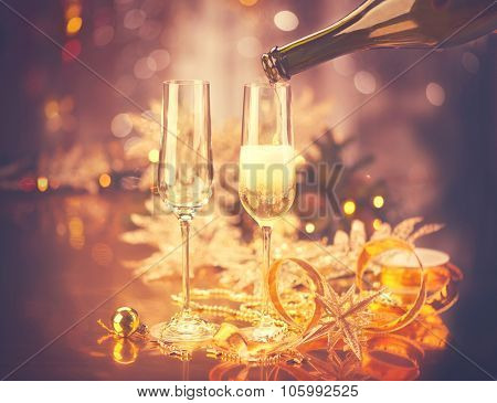 New Year celebration with champagne. Champagne Christmas and New Year celebration. New Year holiday decorated table. Two Champagne Glasses, vintage toned