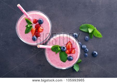 Tasty yogurt decorated with berries and mint on grey background