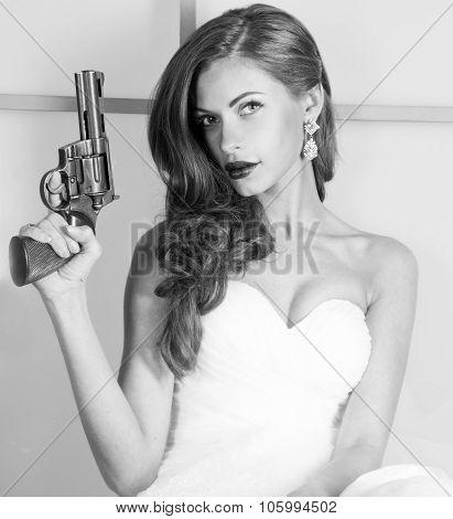 beautiful girl in a wedding dress with a gun