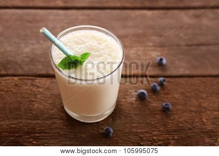 Fresh yogurt with mint and blueberry on wooden background
