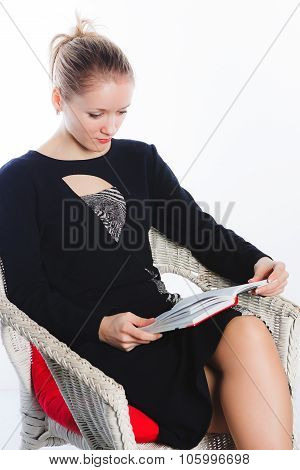 Woman in black dress reads book
