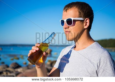 Handsome Man Drinking Beer On The Beach
