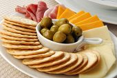 stock photo of pimiento  - A plate of crackers with pimiento stuffed manzanilla olives meats and cheeses - JPG