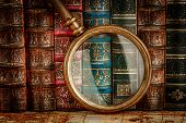 Ancient old books and magnifying glass poster