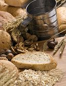 stock photo of flour sifter  - an assortment of whole grain breads with mixed nuts and seeds on a table - JPG