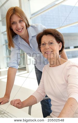 Senior woman with trainer in front of computer