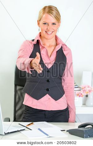 Smiling modern business woman standing near office desk and stretches out hand for handshake