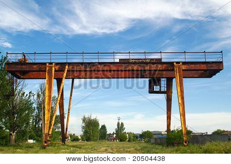 Abandoned Gantry Crane On A Background Of Blue Sky