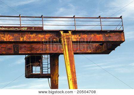 The Cab Is An Abandoned Gantry Crane On A Background Of Blue Sky