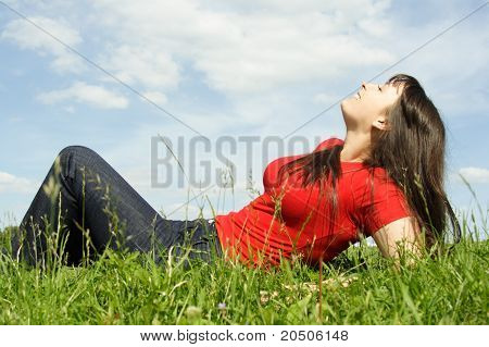 Young Beautiful Girl In Red Shirt And With Long Brunette Hair Lies On Back At Summer Lawn