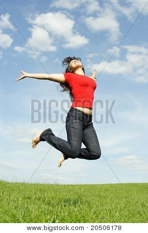 Young Beautiful Girl In Red Shirt And With Long Brunette Hair Jumping At Summer Lawn