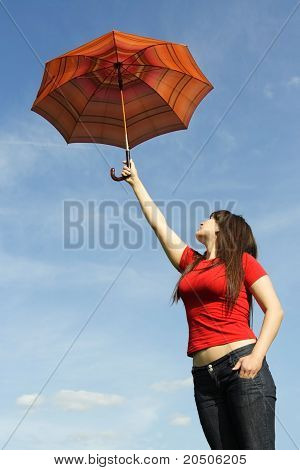 Young Beautiful Girl In Red Shirt And With Long Brunette Hair Holding Umbrella On Stretch Out Hand