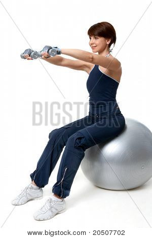 Image of smiling woman doing exercise with barbells on grey ball over white background
