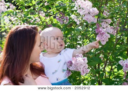 Beautiful Woman With Small Kid And Flowers