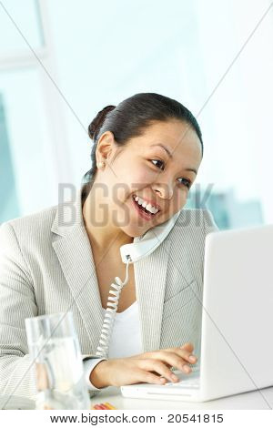 Photo of smart businesswoman calling while typing on laptop keypad
