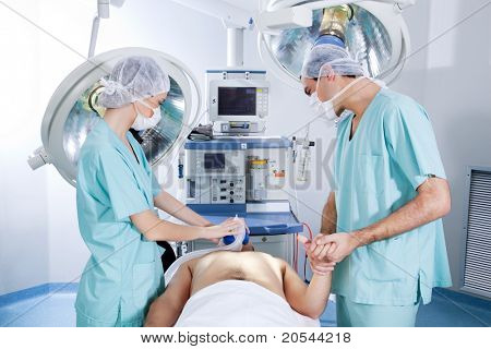 Surgeons operating on patient in an operating theatre