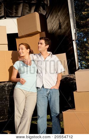 A happy couple with a moving truck and boxes