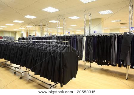 rows of jackets and men trousers on hangers in big light shop