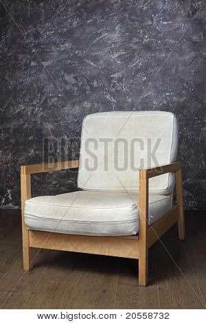 white chair in studio of photographer, brown background, side view