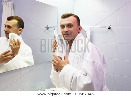 young man in bathroom wearing white bathrobe