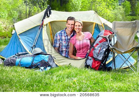 Happy young couple with big tent. Camping.