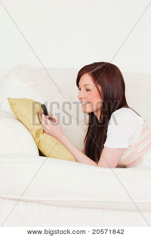 Gorgeous Red-haired Female Writing A Text On Her Phone While Lying On A Sofa