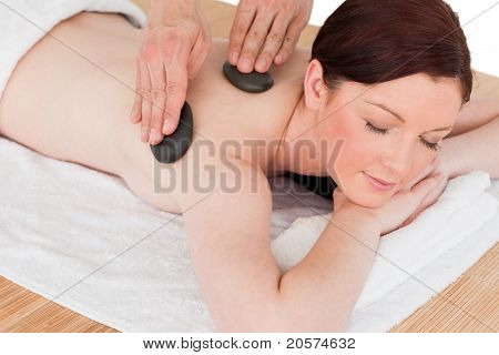 Portrait Of An Attractive Red-haired Female Posing While Receiving A Massage